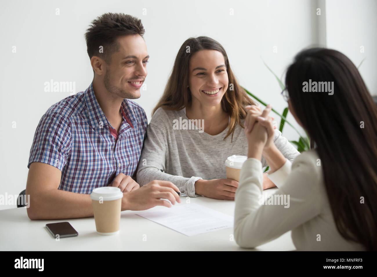 Lächelndes Paar Unterhaltung mit real estate agent Stockbild