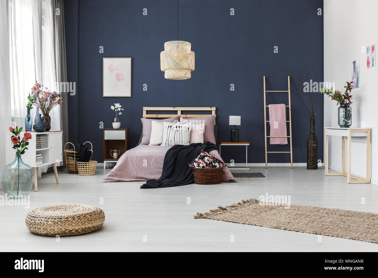 Gemälde hängen an dunkle blaue Wand im gemütlichen Schlafzimmer mit ...