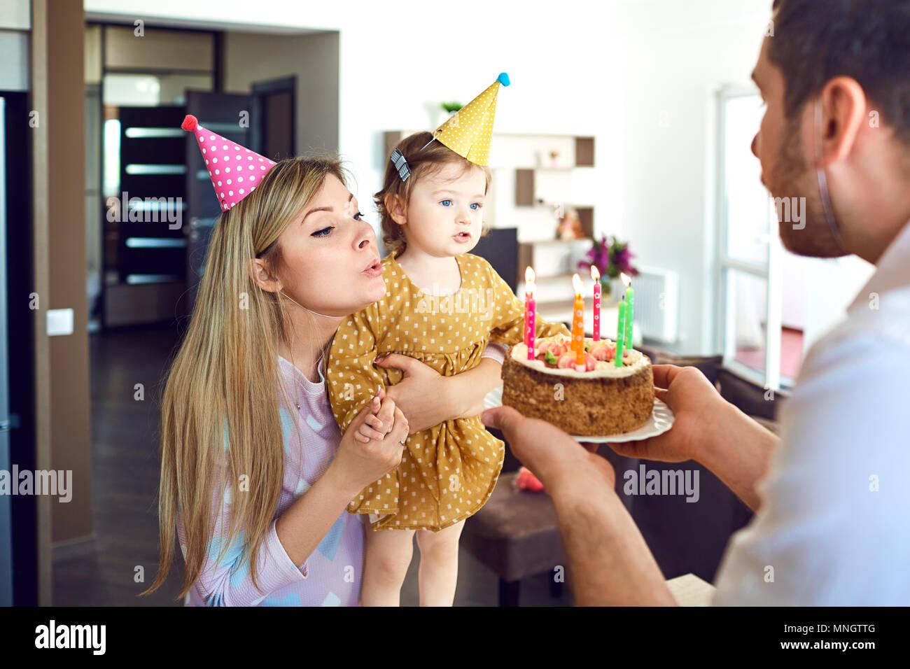 Eine Familie mit einem Kuchen gratuliert ein glückliches Kind an seinem Geburtstag Stockbild