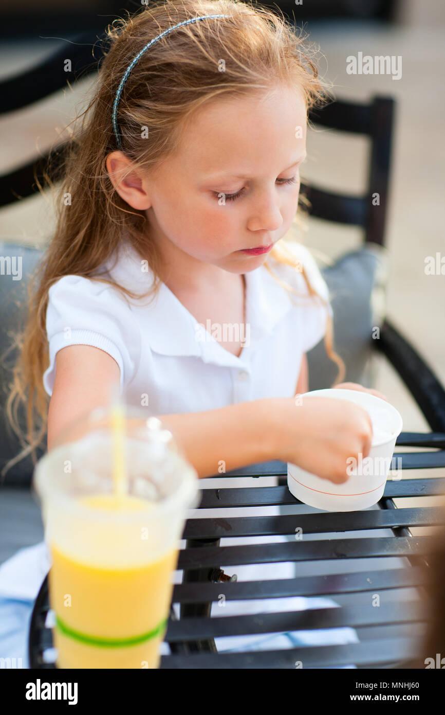 Kleines Mädchen essen ein Eis im Café im Freien Stockbild