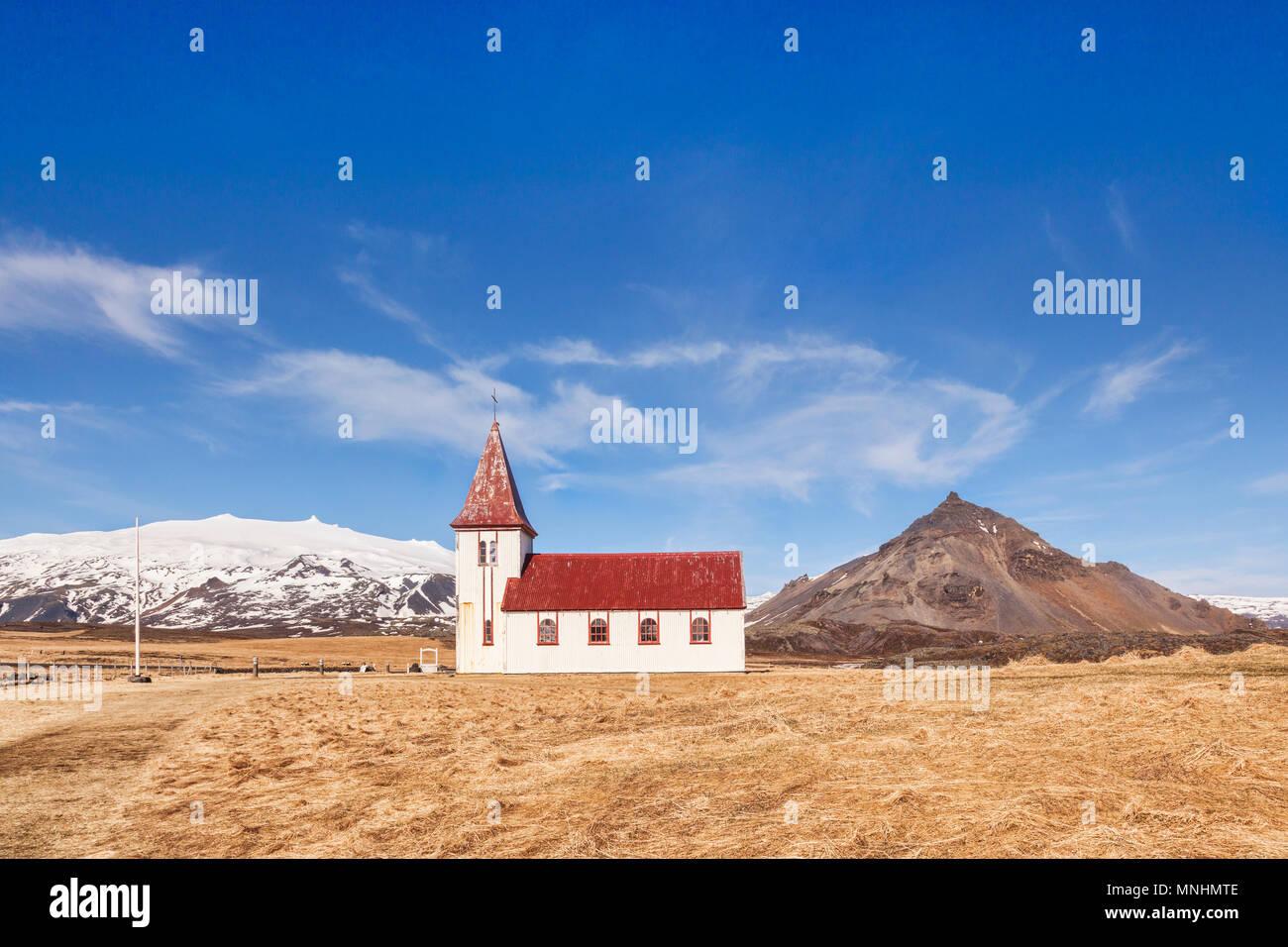 Weiße hölzerne Kirche in Hellnar, Halbinsel Snaefellsnes, West Island. Auf der linken Seite ist der Vulkan Snæfellsjökull, mit Schnee bedeckt, und auf der rechten Seite ist Stockbild
