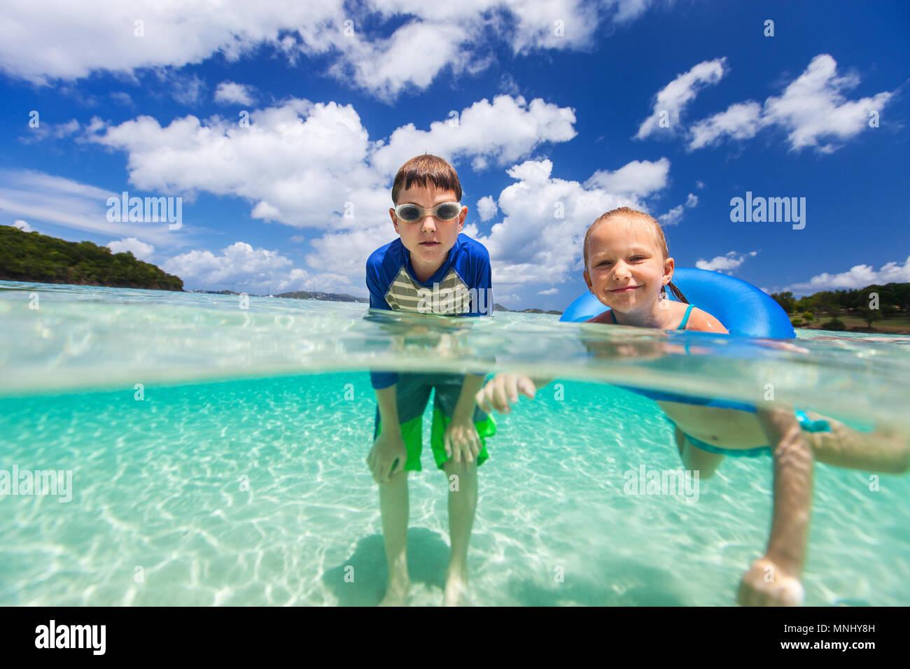 Split Unterwasser Foto der süßen kleinen Mädchen und niedlichen Jungen planschen in einem tropischen Meer Wasser in den Sommerferien Stockfoto