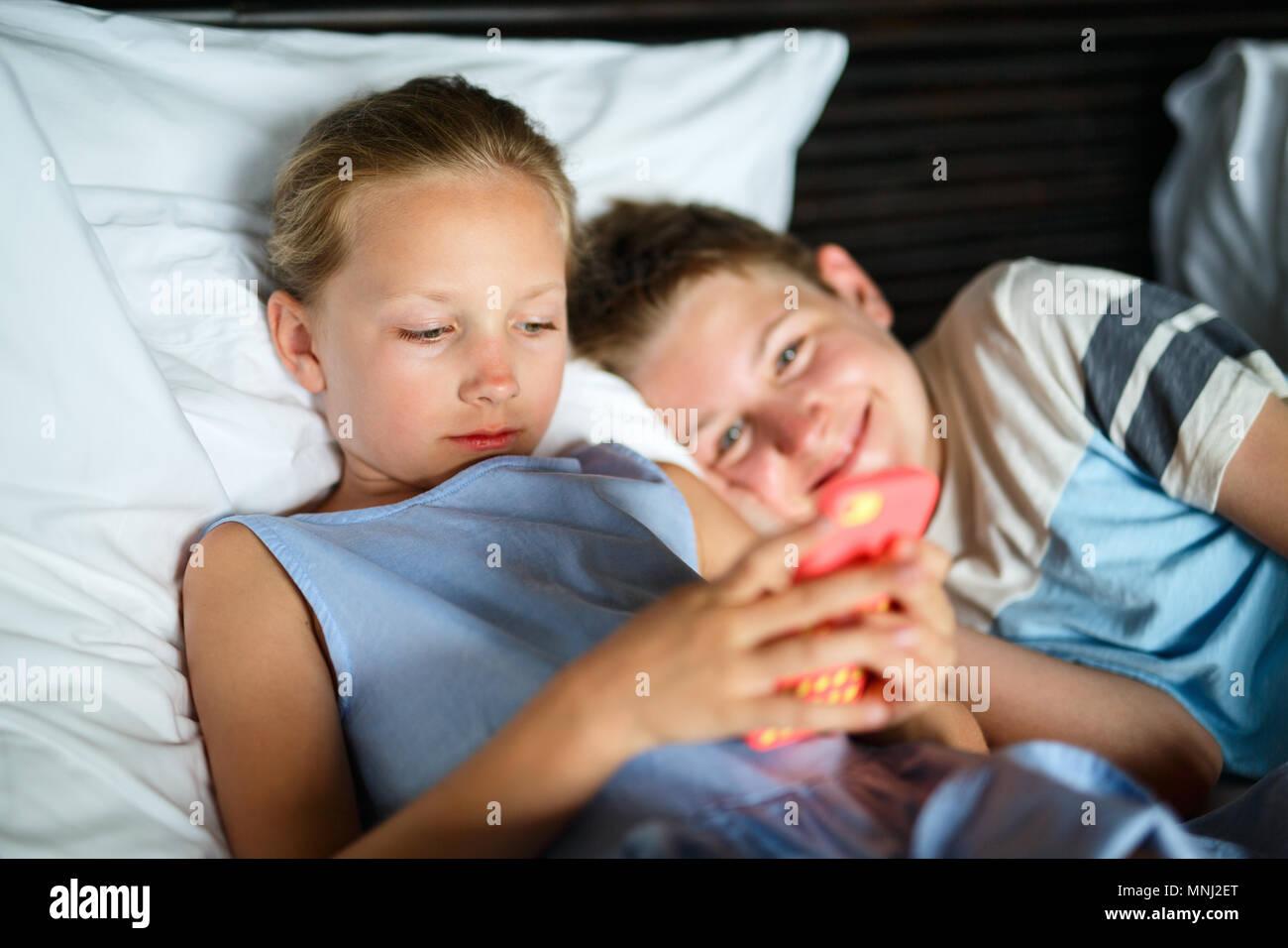 Kinder Bruder und Schwester spielen auf einem tragbaren Spiel Gerät oder Smartphone Stockbild