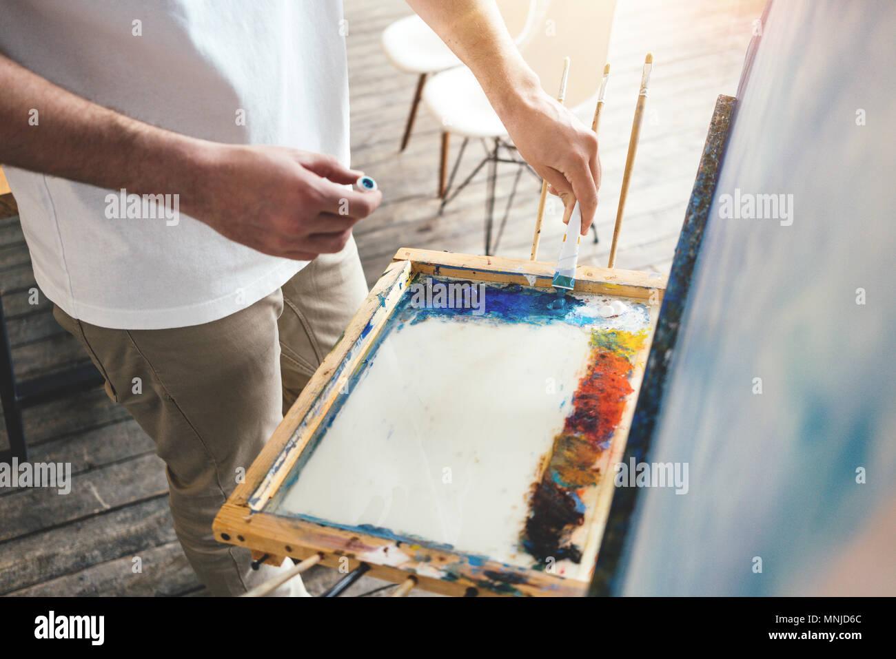 Maler mischt die Farben auf der Palette in der Werkstatt. Männer Künstler in Light Studio. Lens flare Effekt Stockbild