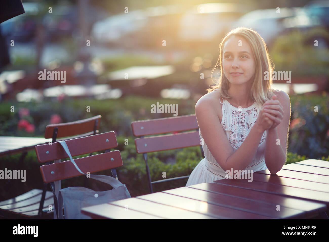 Schöne kaukasische Frau am Tisch sitzen Stockfoto