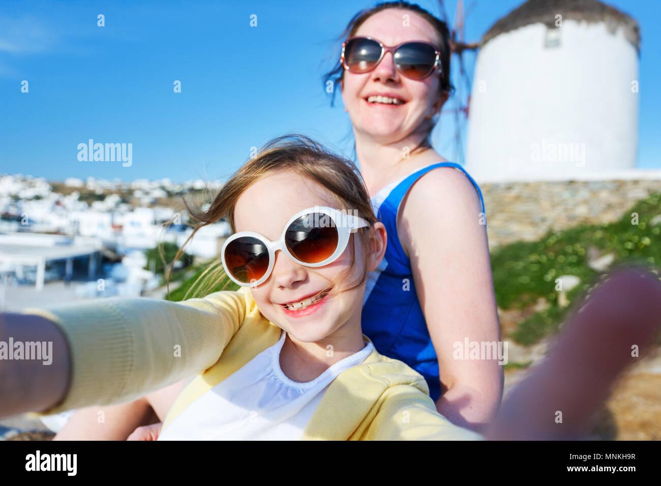 Glückliche Familie Mutter und ihre süßen kleinen Tochter auf den Urlaub nimmt selfie auf Klein Venedig Bereich auf der Insel Mykonos, Griechenland Stockbild