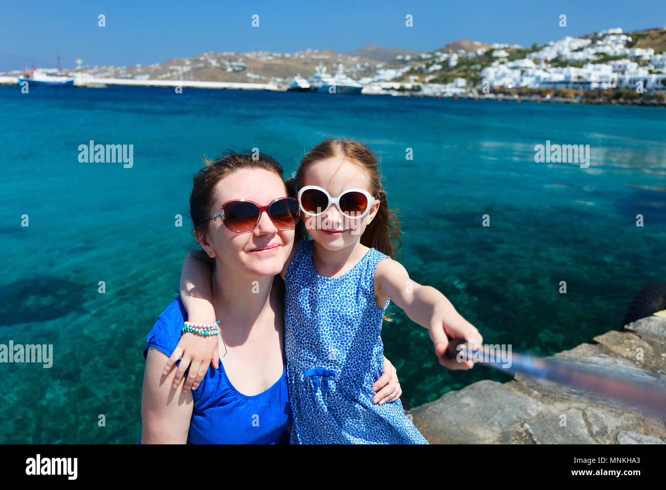 Glückliche Familie Mutter und ihre süßen kleinen Tochter auf den Urlaub nimmt selfie mit einem Stock auf der Insel Mykonos, Griechenland Stockbild