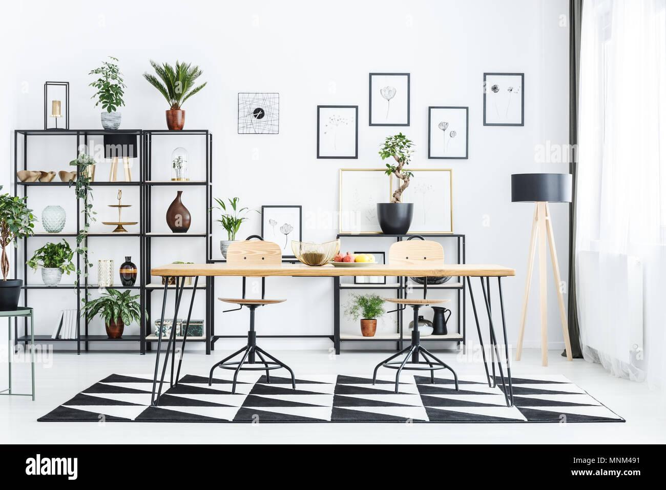 Holz Stuhl am Tisch, auf geometrische Teppich in scandi Esszimmer Innenraum mit Lampe Stockbild