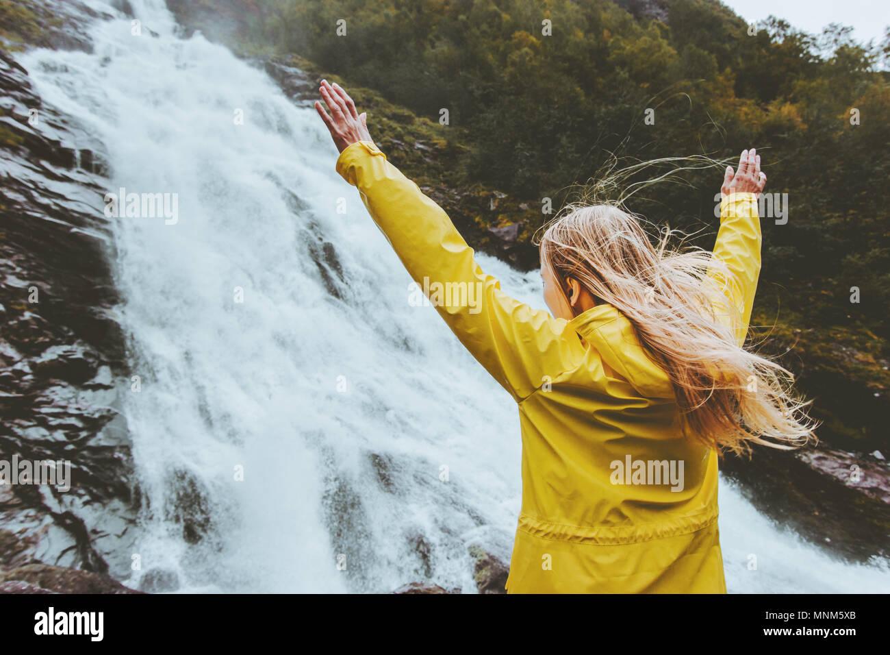 Reisende Frau erhobenen Händen genießen Wasserfall Landschaft allein Reisen in das wilde Abenteuer Lebensstil in Harmonie mit der Natur begriff emotionale expre Stockbild