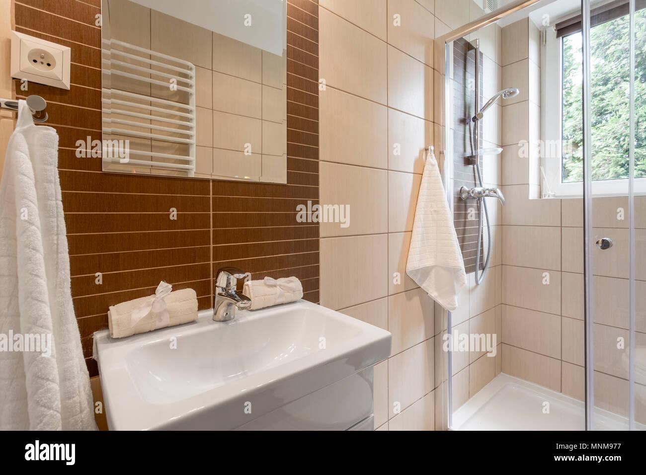 Kleines Badezimmer mit braunen Fliesen, Spiegel, Dusche und ...
