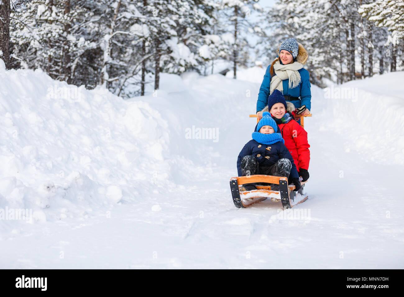 Schöne Familie von Mutter und Kinder genießen schneereiche Winter Tag im Freien Spaß Schlittenfahren Stockbild