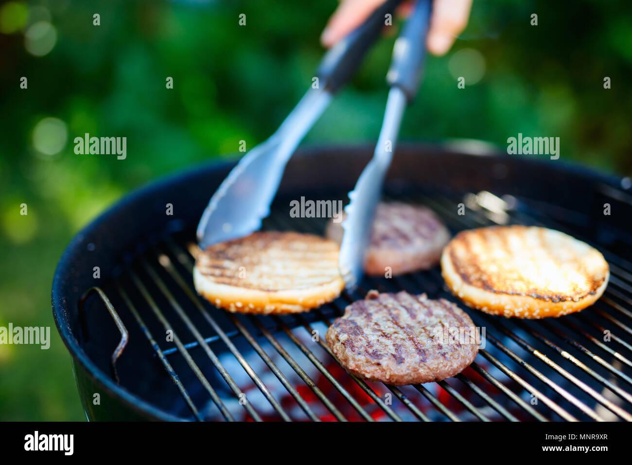 Das Grillen von frischen Brötchen und Burger Fleisch Schnitzel für hausgemachte Burger Kochen im Freien im Sommer Tag Stockbild