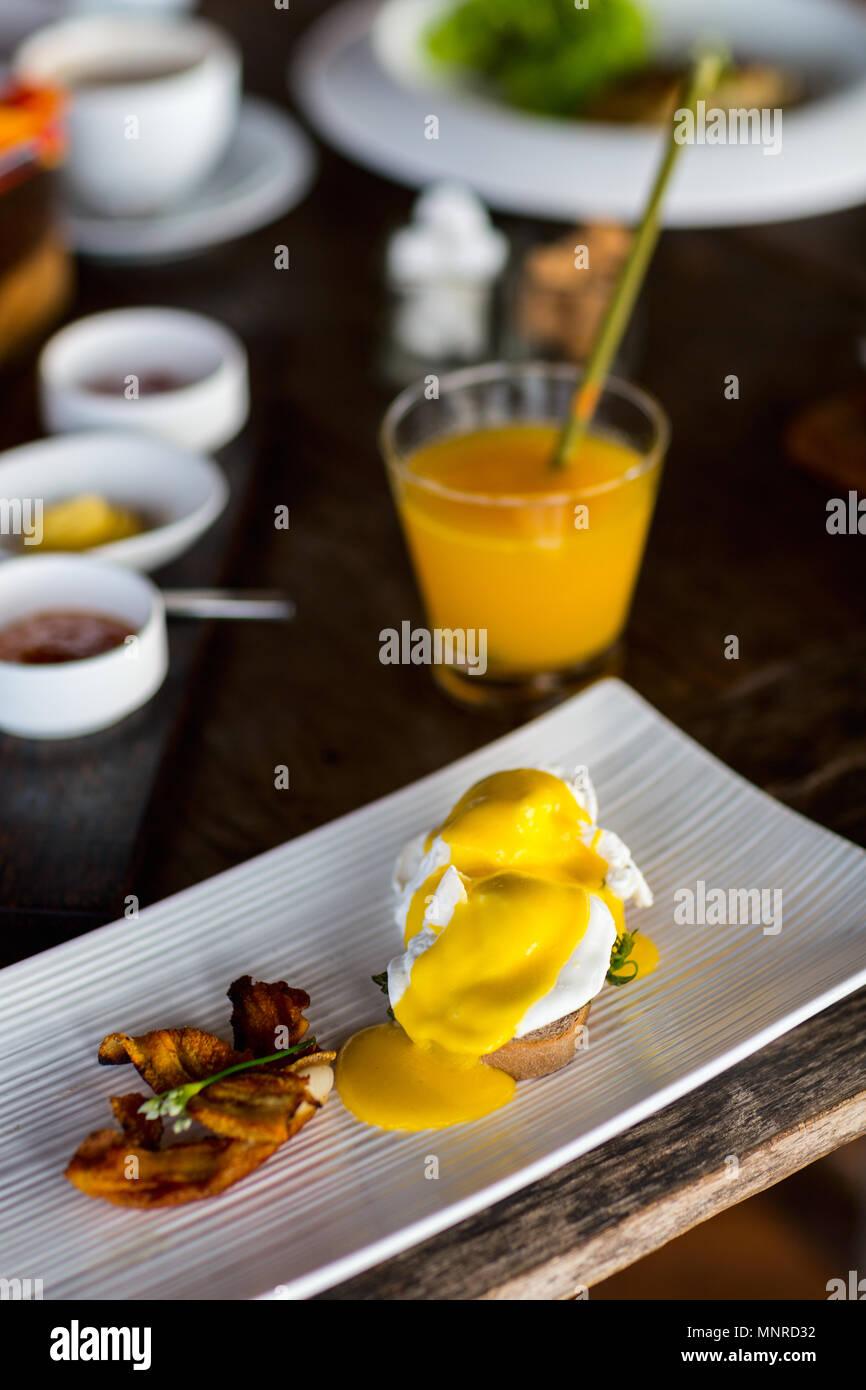 Köstliches Frühstück mit Eggs Benedict und Speck Stockbild