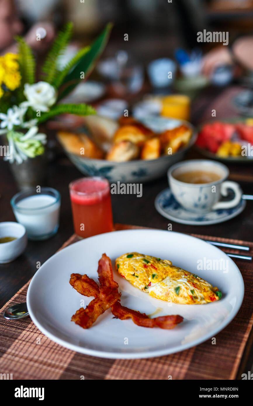 Köstliches Frühstück mit Omelettes, Speck und Gemüse Stockbild