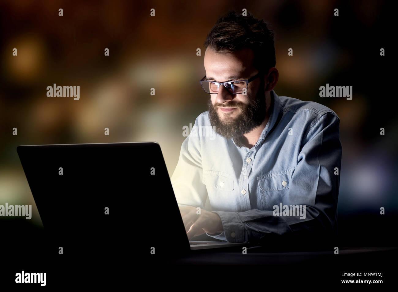 Junge gut aussehender Geschäftsmann spät in der Nacht die Arbeit im Büro Stockbild