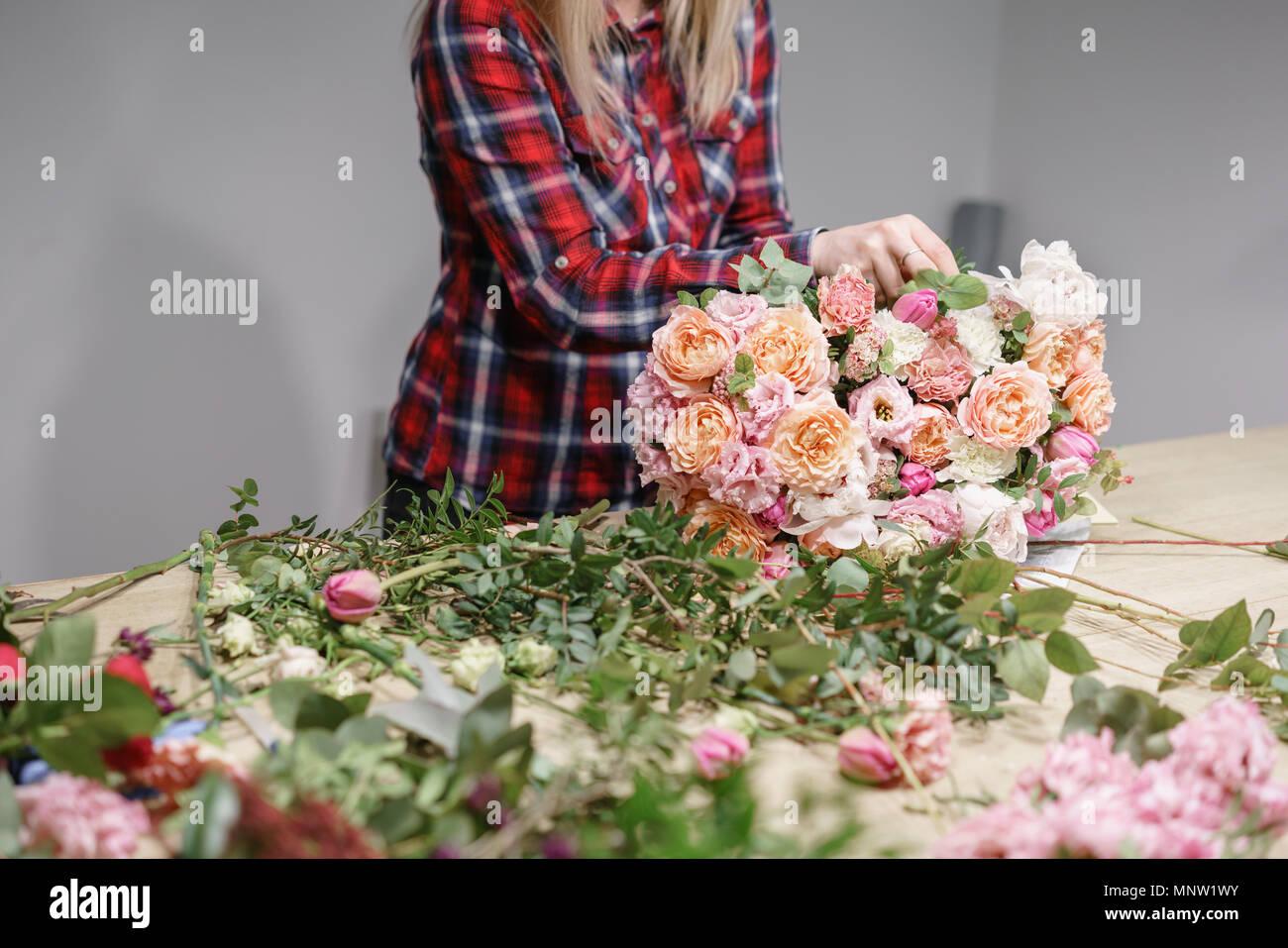 Weibliche Florist. Florale Werkstatt - Frau, die eine schöne Blume Komposition einen Blumenstrauß. Floristik Konzept Stockbild