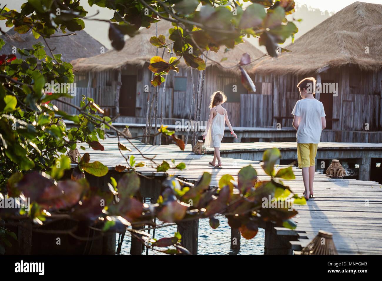 Kinder Bruder und Schwester auf dem Holzsteg im Sommer Urlaub in Luxus Resort Stockbild