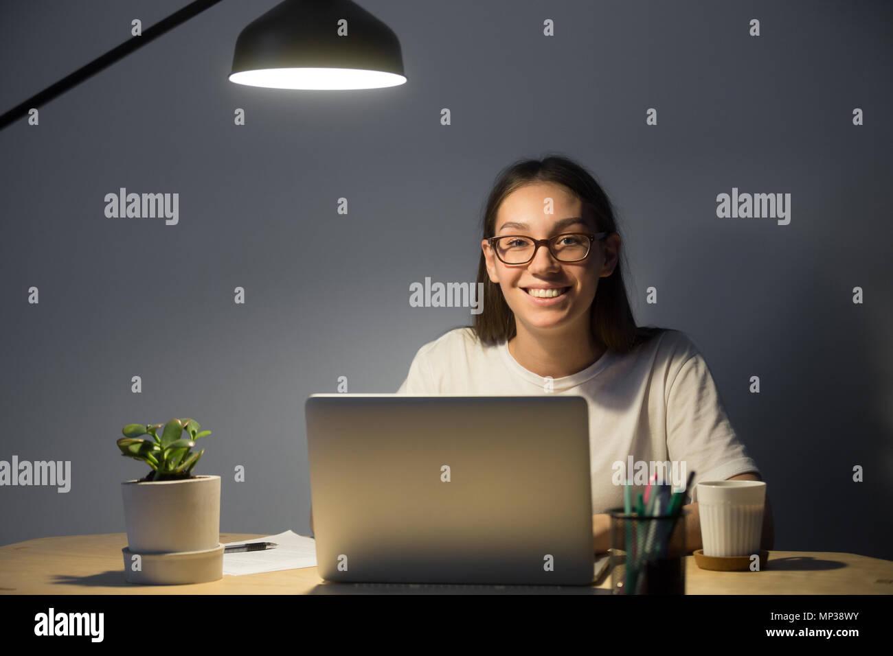 Freelancer glücklich lächelnd in die Kamera im Büro Schreibtisch posing Stockbild