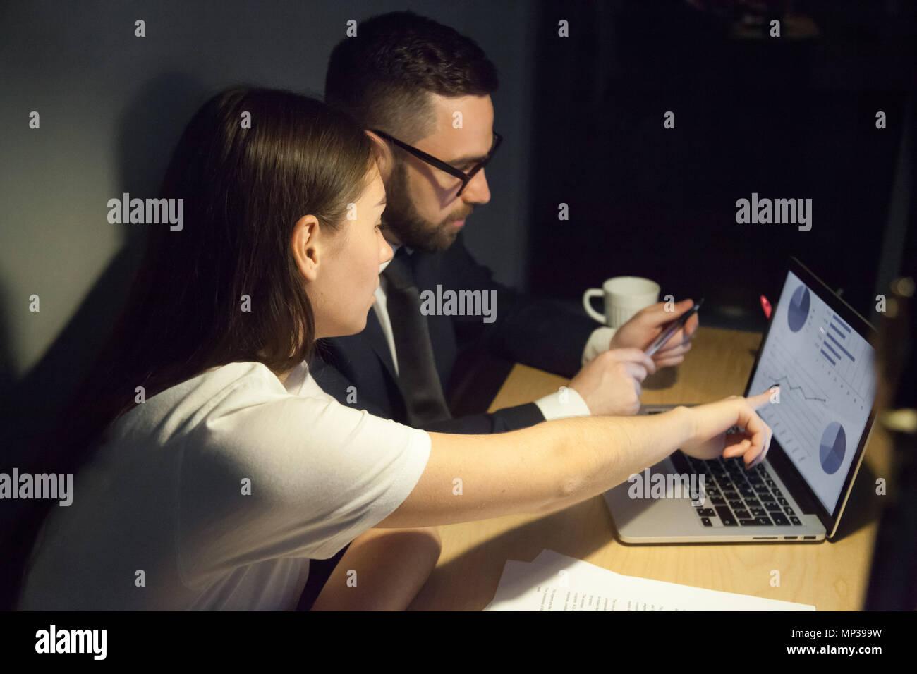 Fokussierte Kollegen analysieren die Gewinne der Unternehmen arbeiten zu spät aus Stockbild