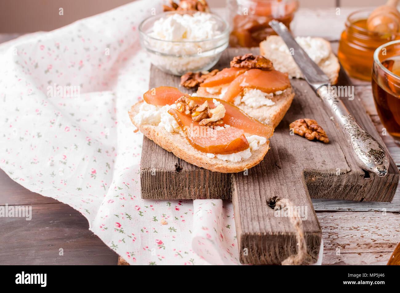 Frühstück. Tee mit Sandwiches mit ricotta Käse und pear Jam. Tasse Kaffee und Teekanne aus Glas. Ansicht von oben, kopieren Raum Stockfoto