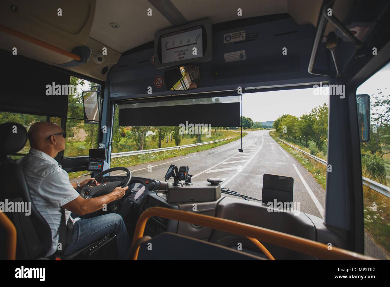 Thema ist der Beruf des Treibers und der Personenbeförderung. Ein Mann in Sonnenbrille einen Treiber, der eine touristische Regional Bus in Frankreich Region der Laufwerke Stockbild