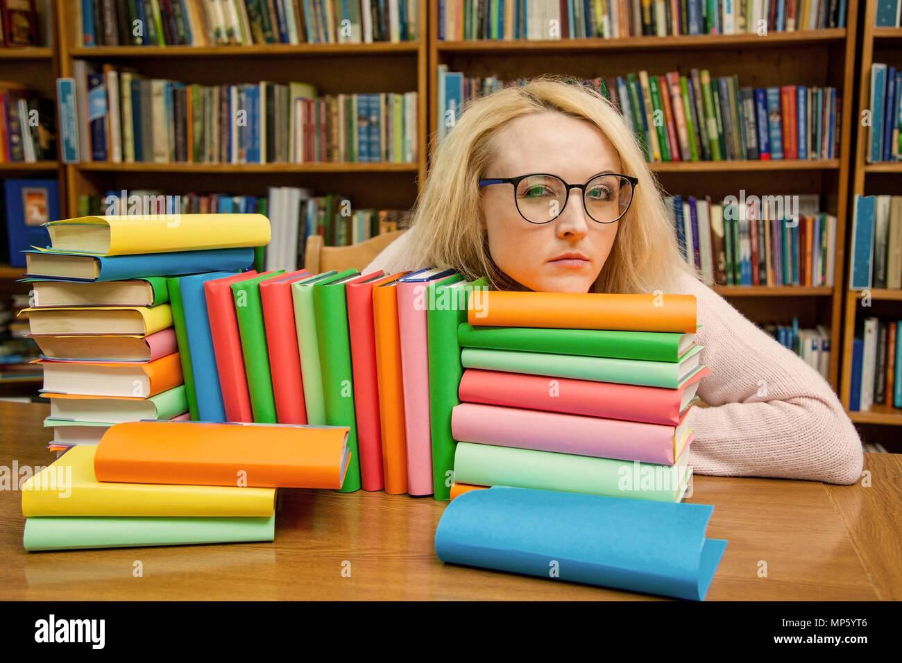 Ein Mädchen in der Bibliothek sieht geheimnisvoll durch Gläser Stockbild