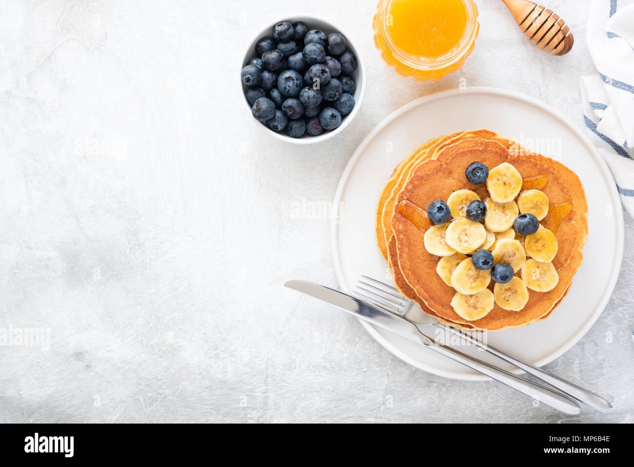 Buttermilch Pfannkuchen mit Banane, Blaubeeren und Honig auf konkreten Hintergrund. Ansicht von oben und kopieren Sie Platz für Text. Blick von oben auf die Pfannkuchen mit Beeren auf Stockbild