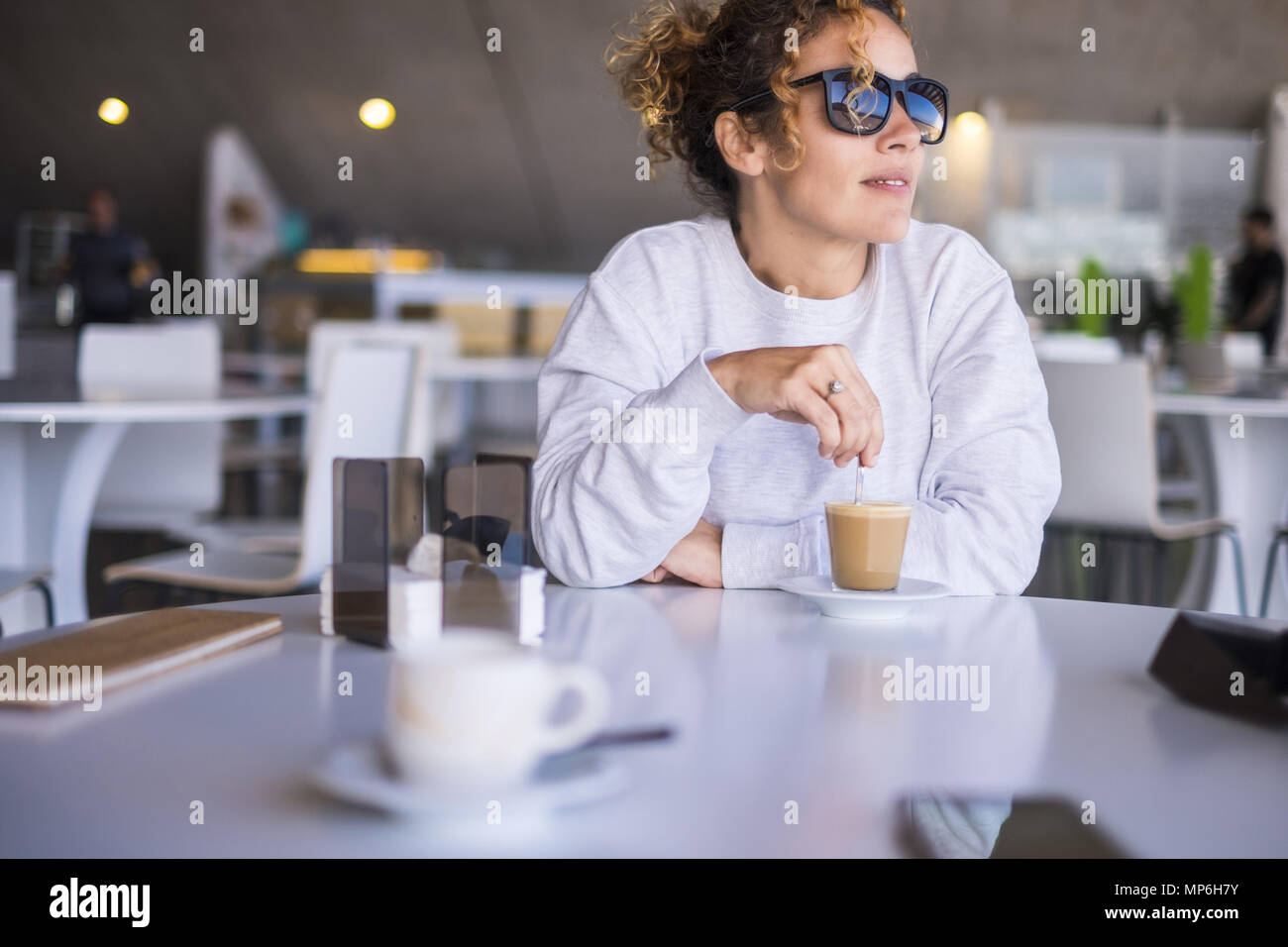 Schönen kaukasischen Frauen mittleren Alters mit Sonnenbrille, und trinken Sie einen Kaffee in einer Bar. outdoor Licht vom Fenster für eine Freizeit rest Moment während des Stockbild