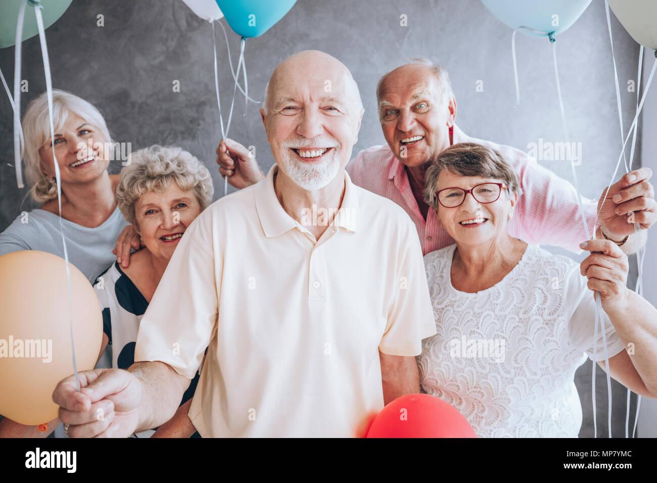 Lächelnd älterer Mann und seine Freunde mit Ballons mit seiner Geburtstagsfeier Stockfoto