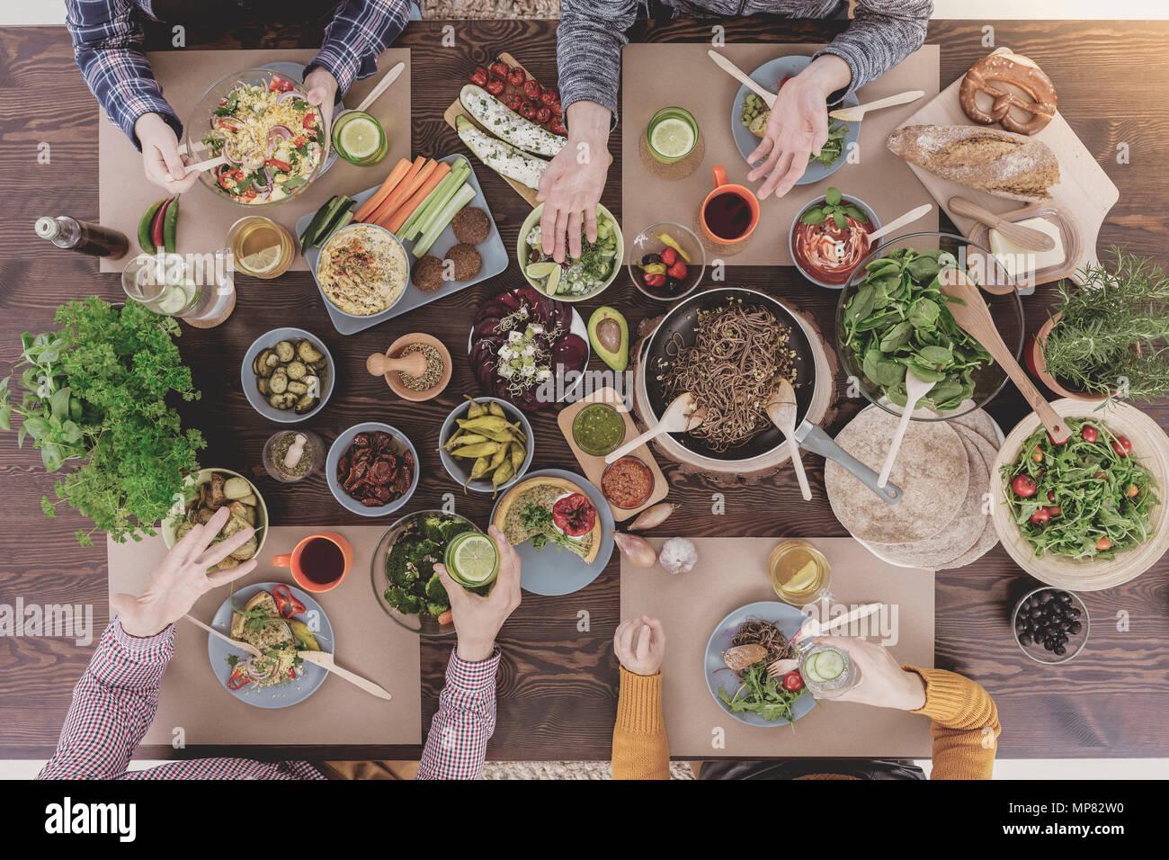 Verschiedene vegetarische Gerichte liegen auf Holztisch, Ansicht von oben Stockbild
