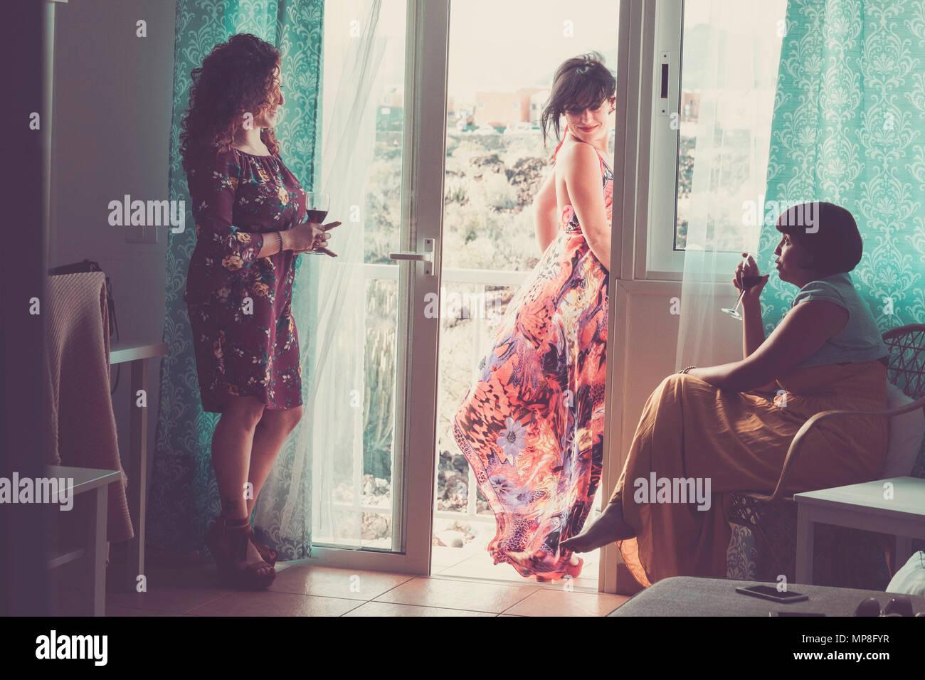 Drei kaukasischen mittleren alter Freunde zu Hause in einer üblichen Tag. zwei Innen- und einem outsdide auf der Terrasse sprechen zusammen Trinken einer Tasse Wein Stockbild