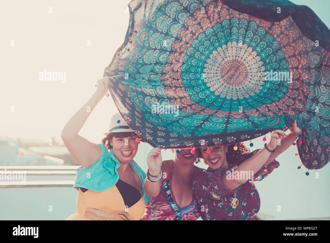Drei junge schöne weibliche Damen nehmen ein Mandala Textil über die Köpfe. Spielen mit dem Wind in Aktivität im Freien. Sommer Konzept mit Sun backligh Stockbild