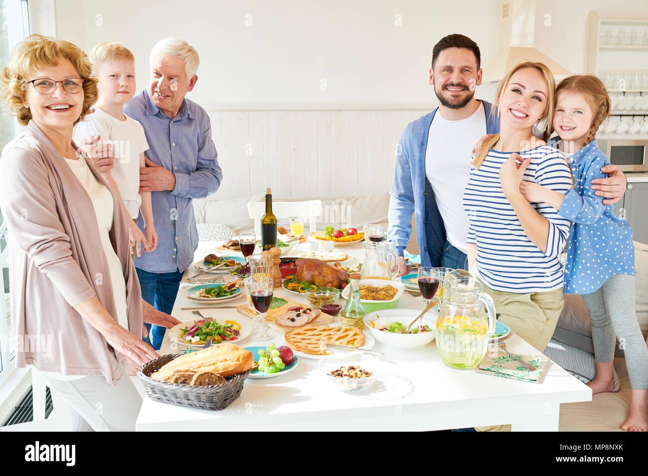 Große, glückliche Familie posiert am Tisch Stockfoto