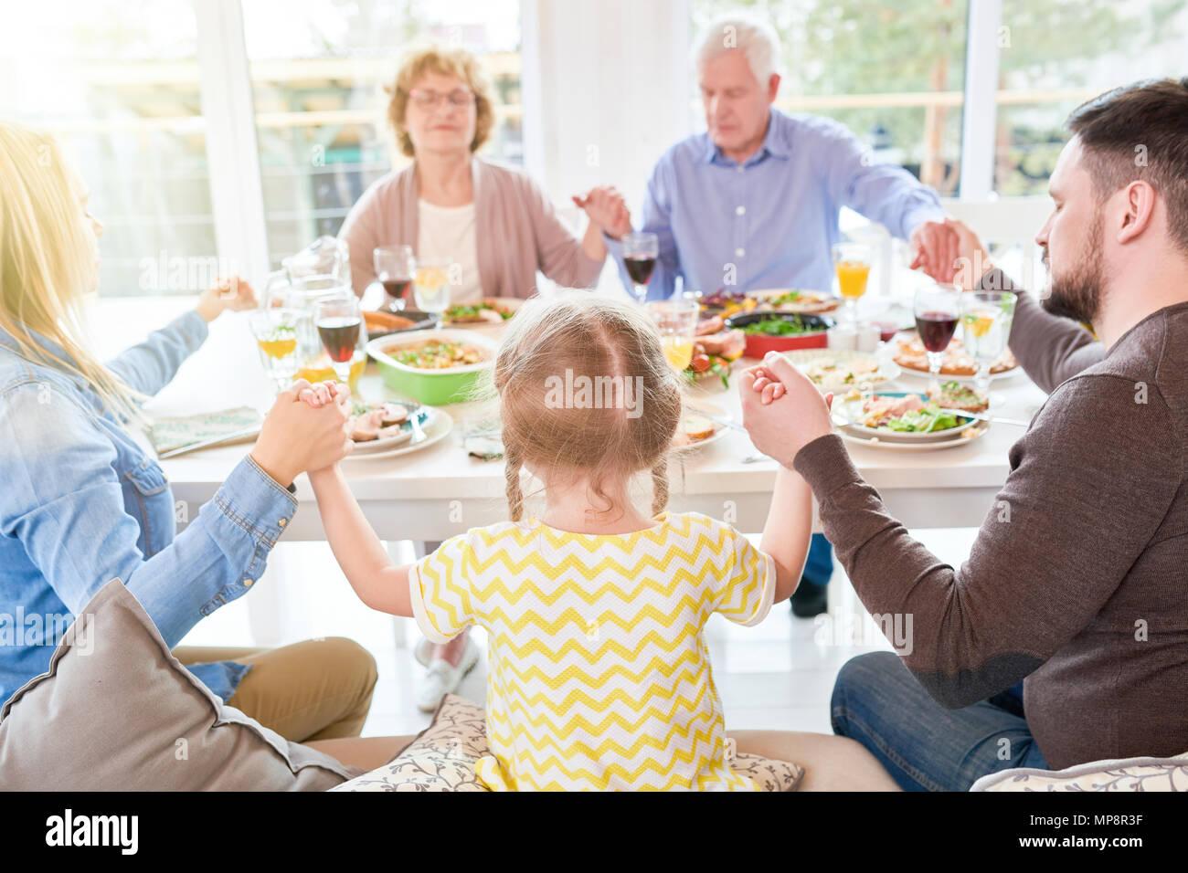 Familie beten bei Abendessen mit der Familie Stockbild