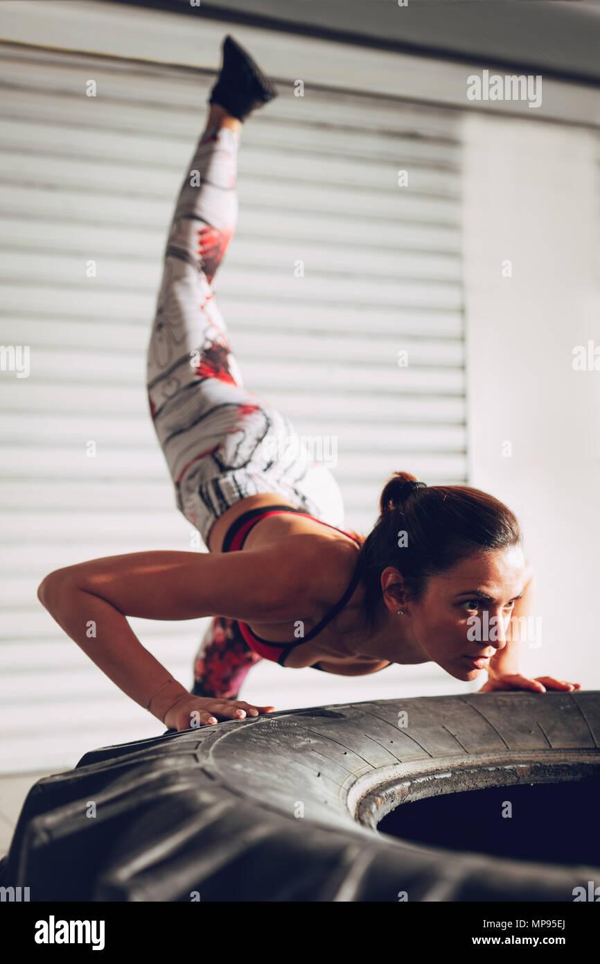 Junge Muskulöse Frau, Push Up Übung Auf Einem Reifen An Hartes Training In