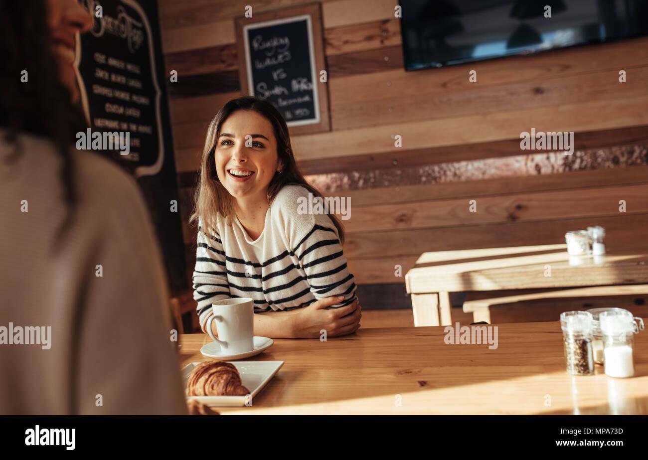 Lächelnde Frau in einem Restaurant sitzen im Gespräch mit ihrer Freundin. Freunde in einem Café mit Kaffee und Snacks auf den Tisch sitzen. Stockfoto