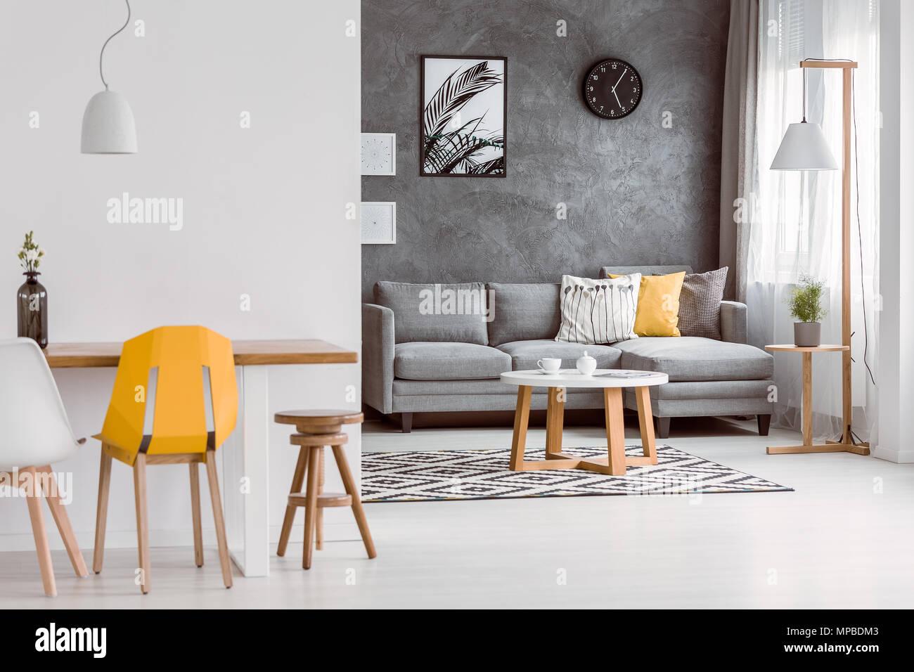 Gelbe Stuhl Bei Hölzernen Tisch In Modernes Wohnzimmer Mit Dekorativen  Kissen Auf Grau Sofa