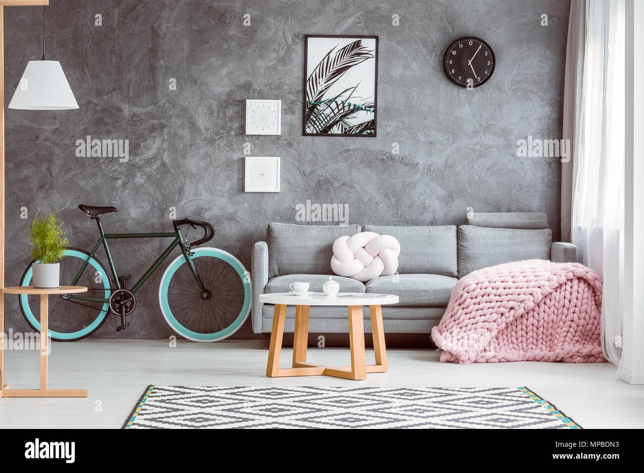 Fahrrad mit Blue Wheels im gemütlichen Wohnzimmer mit Rosa gestrickte Decke und Kissen auf grau Sofa Stockfoto
