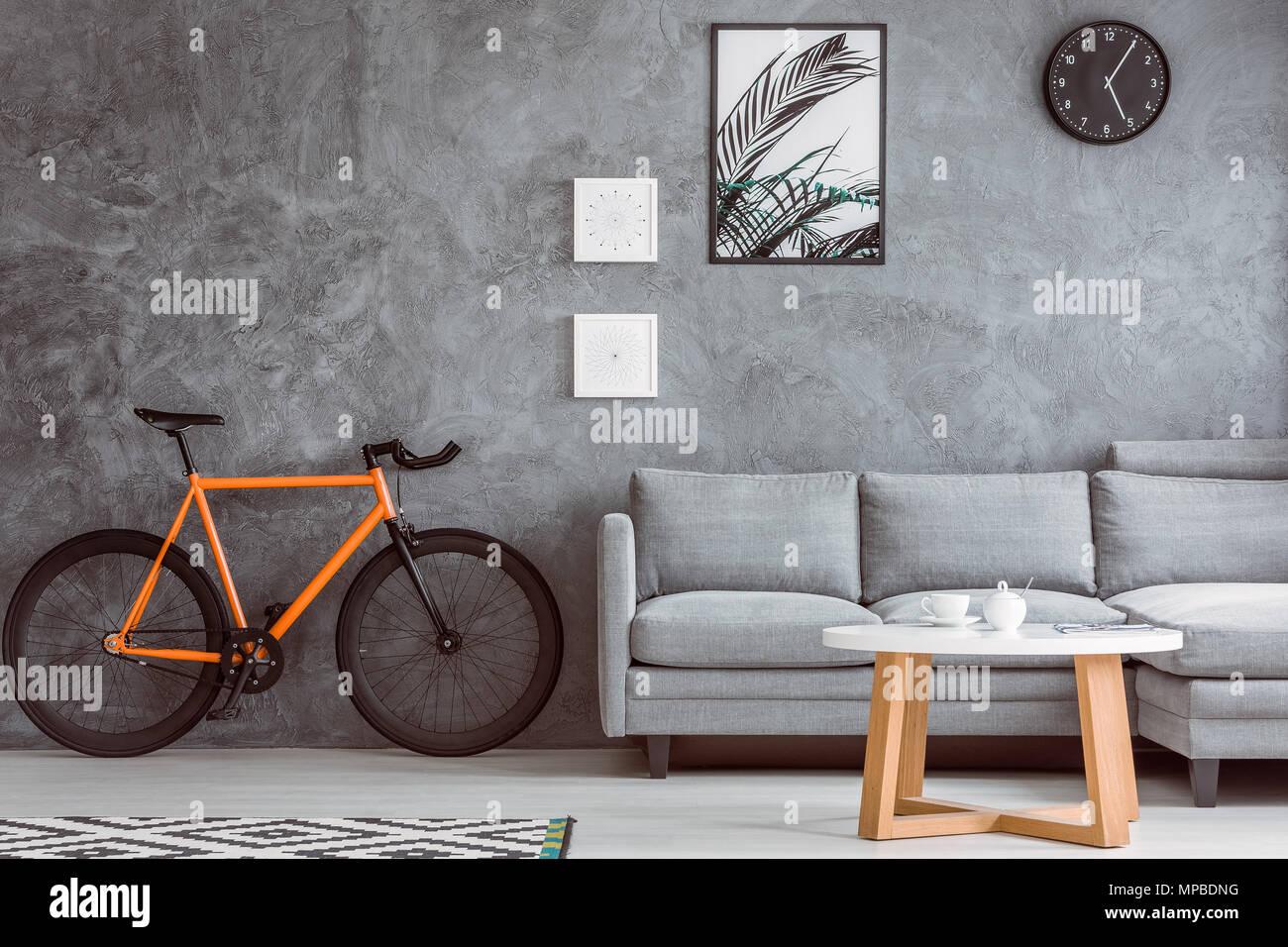 Orange bike Neben grau Sofa im Wohnzimmer mit Tisch, schwarz, Wecker ...
