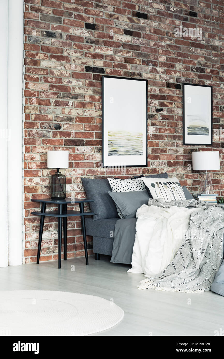 Hochwertig Zwei Poster Aufhängen An Die Wand Im Schlafzimmer Im Loftstil Mit Lampe Auf  Dem Nachttisch