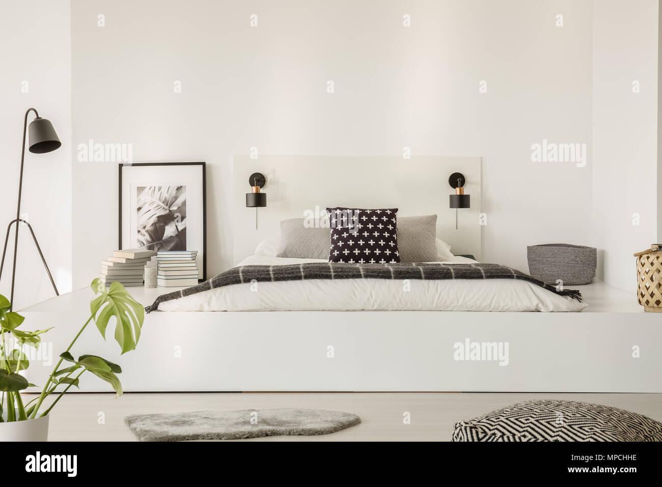 Echten Foto Von Einem Bett Mit Weißer Bettwäsche, Schwarz Kissen Und Graue  Decke Auf Einer Plattform In Modernes Schlafzimmer Innenraum