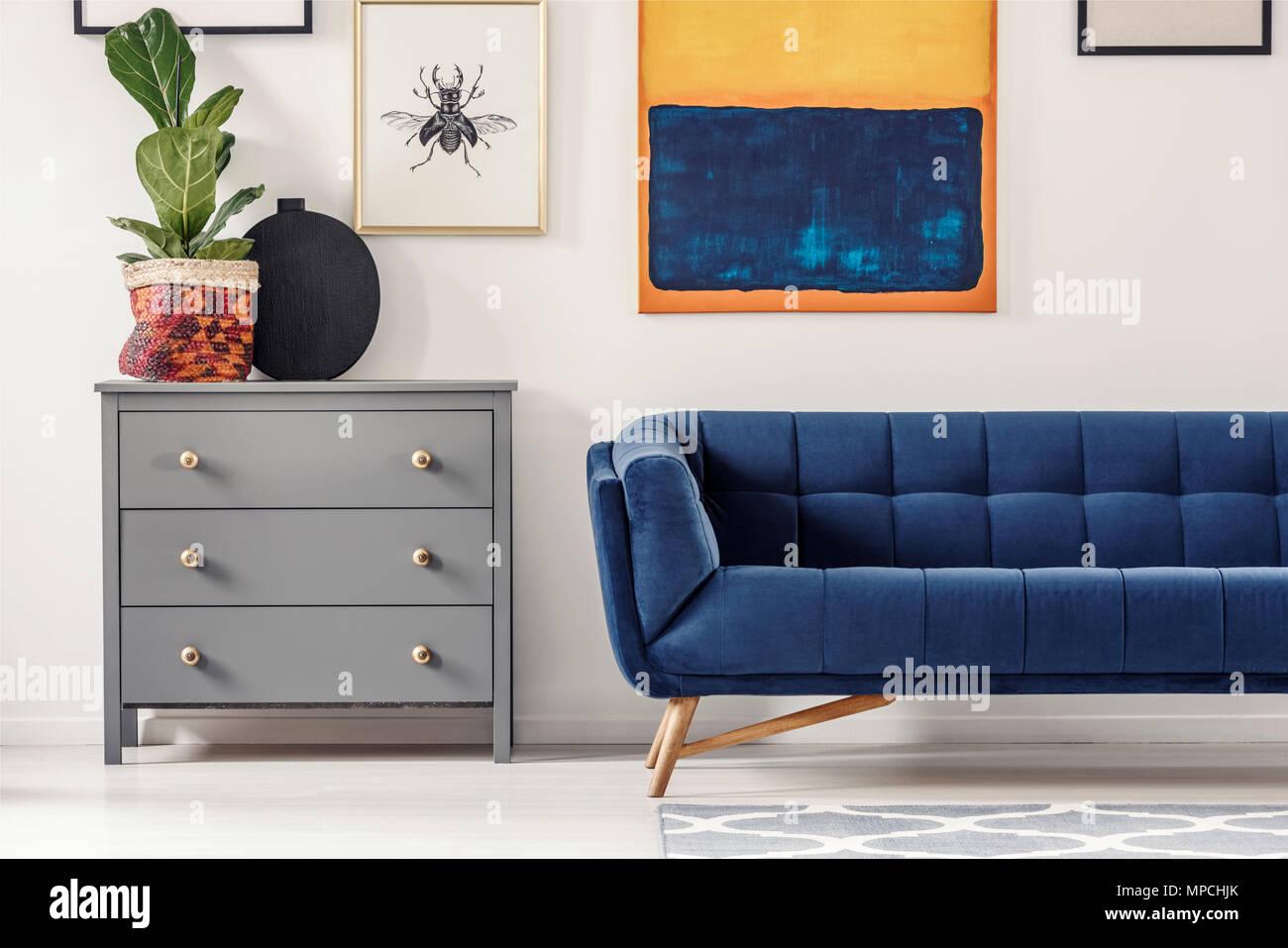Frisches Grün auf grau Kabelschleusen neben Navy blaues Sofa im ...