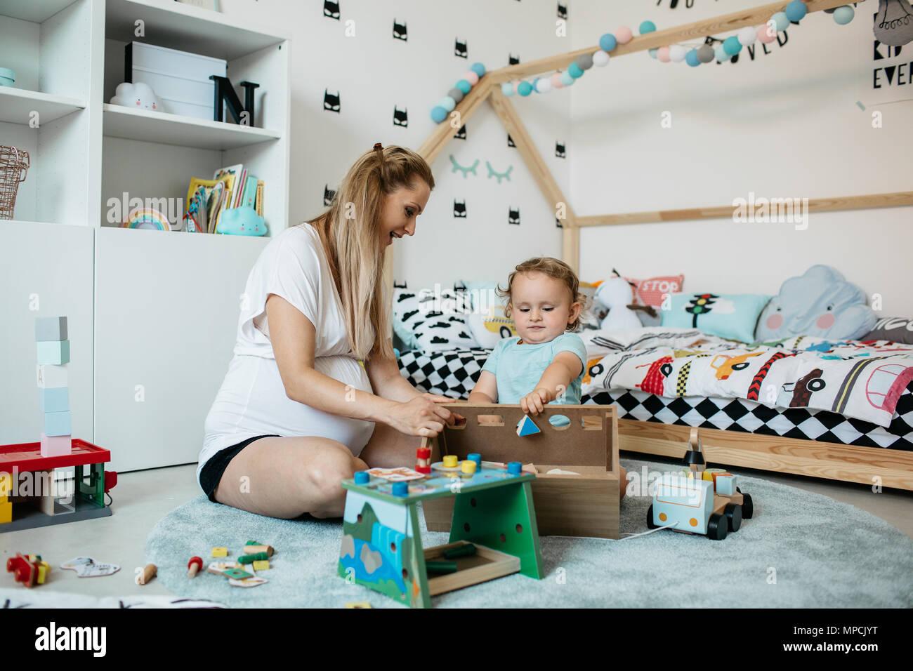 Eine Mutter bringt ihr Kind geometrischen Formen und Farben. Ein kleiner Junge versucht, geometrischen Formen und seine Mutter ihm ermutigende Art. Stockbild