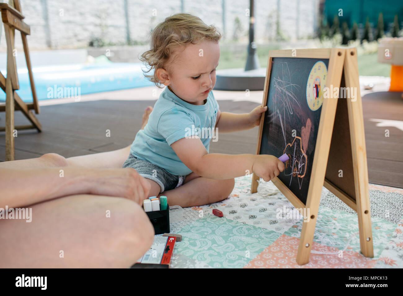 Ein Kleinkind genießen selbst Zeichnen auf einem schwarzen Brett. Ein kleiner Junge kritzeln mit Kreide auf einer Tafel. Stockbild