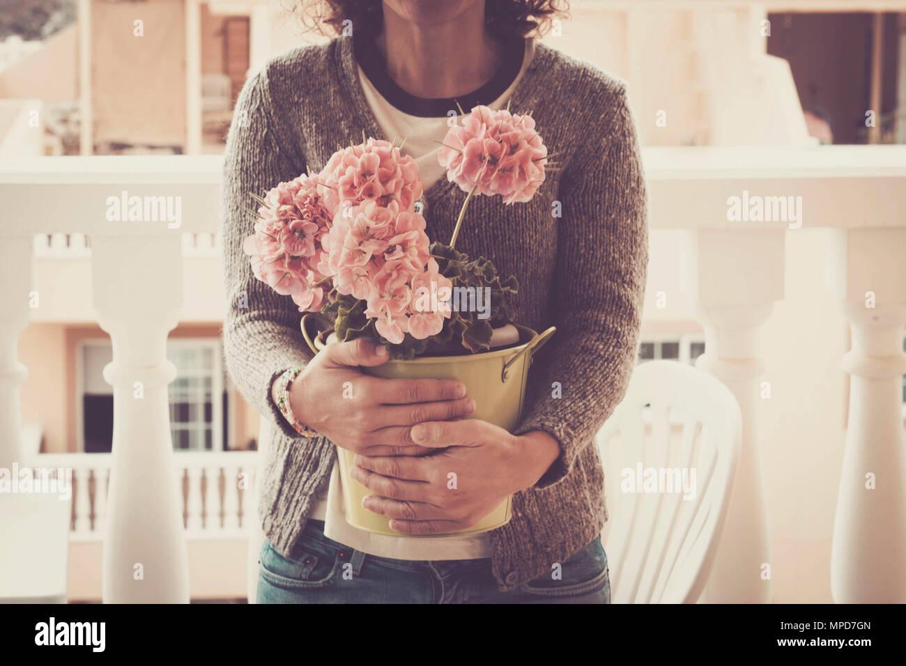Kaukasische Frau mittleren Alters mit großen Vase mit Blumen im Freien auf der Terrasse mit Sonnenlicht. Romantische bohemien Konzept hippy Lebensstil Stockbild