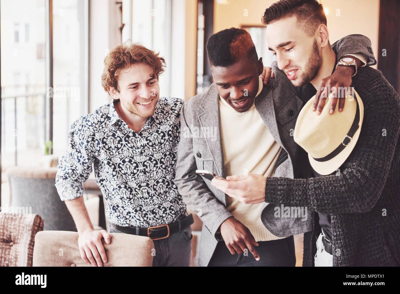 Freundliche alte Freunde untereinander und Telefon beobachten, die im Pub zu kommunizieren. Konzept der Unterhaltung und Lifestyle. Wlan verbunden Menschen in bar Tisch Stockbild