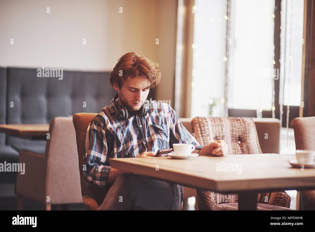 Glücklicher mann Inhaber der gemütliches Cafe fröhlich in eigenen Erfolg beim Sitzen mit Touch Pad am Esstisch, lächelnden Mann halten digitale Tablet und denkt über etwas Gutes während der Mittagspause im Café Stockbild