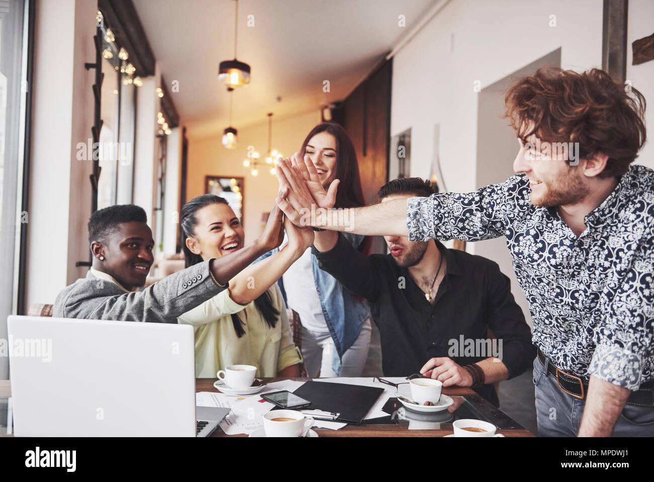 Glückliche junge Unternehmer in Freizeitkleidung im Cafe Tabelle oder im Business Office geben High Fives zu einander, als ob Erfolge feiern oder Starten neues Projekt Stockbild