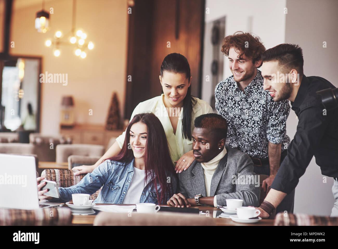 Multi-ethnische Geschäftsleute, Unternehmer, Business, Small Business Konzept, Frau, Kollegen etwas auf Laptop, wie sie um einen Konferenztisch sammeln Stockbild