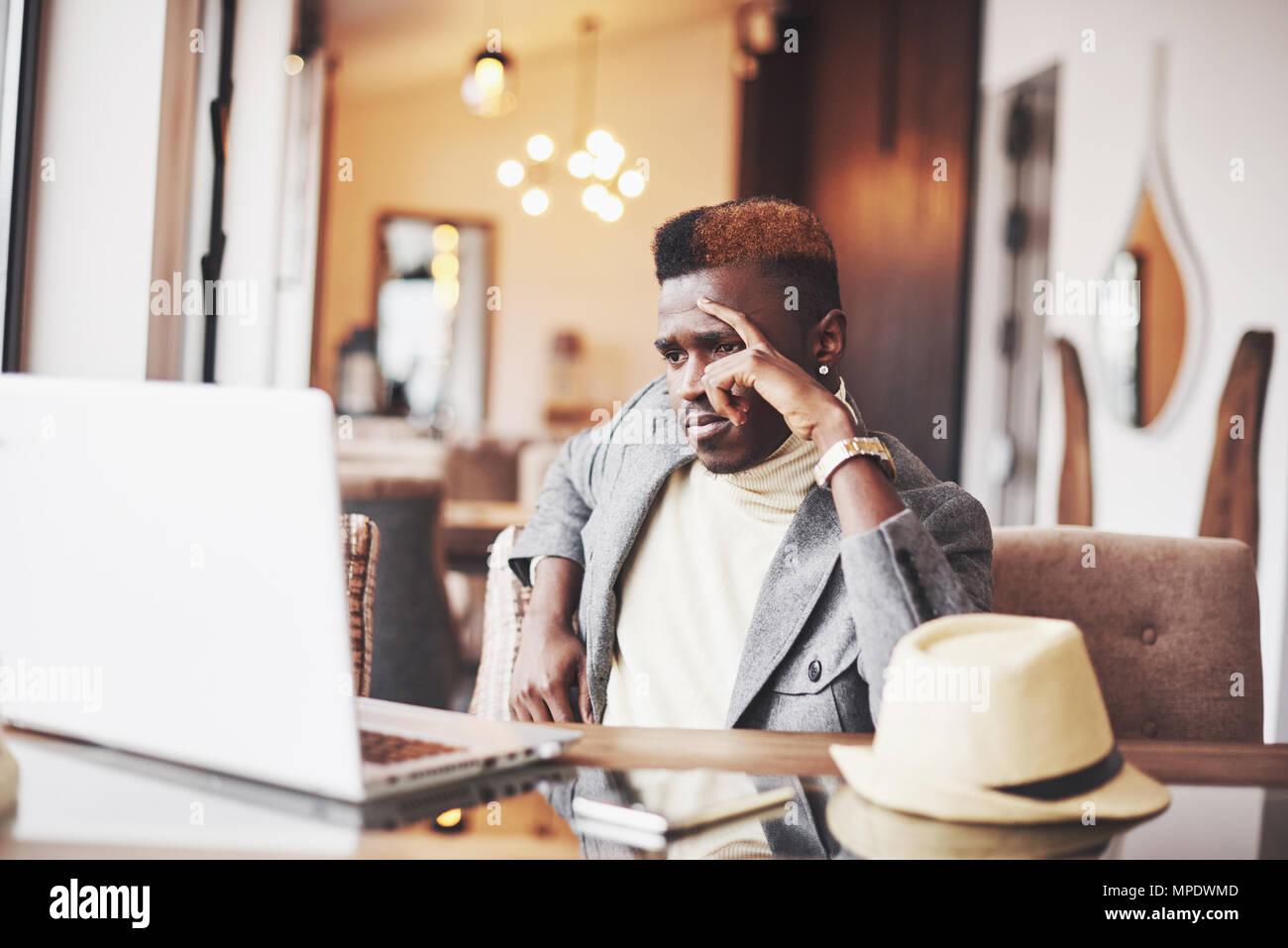 Nachdenklich, afro-amerikanische stattlichen professioneller Schriftsteller der beliebtesten Artikel im Blog im trendigen Outfit gekleidet und Gläser denken über neue Geschichte Korrekturlesen sein Skript von Notebook im Cafe sitzen Stockfoto
